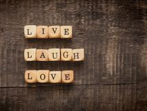 Live laugh love concept. Wooden dices with the words live laugh love on a wooden background Stock Image