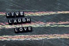 Live Laugh Love em blocos de madeira Imagem processada transversal com fundo do quadro-negro imagens de stock royalty free
