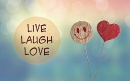Live laugh love with heart and smile emoji. Live laugh love with wooden heart and smile emoji on bokeh light background royalty free stock image