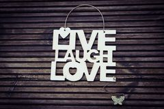 Live Laugh Love. Uplifting sign on a wooden background Royalty Free Stock Images