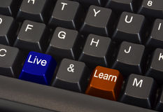 Live and learn concept. On black keyboard with blue and orange colored keys Stock Images