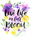 Live life in full of bloom. Inspirational saying, hand lettering card with warm wishes. Watercolor flowers and brush. Calligraphy. Bright yellow, purple and Stock Photos