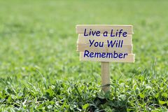 Live a life you will remember. Wooden sign in grass,blur background stock photography