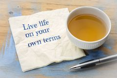 Live life on your own terms - advice on napkin. Live life on your own terms - inspirational handwriting on a napkin with a cup of tea stock images