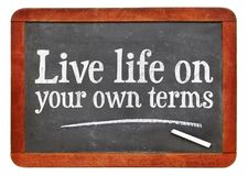 Live life on your own terms. White chalk text on a vintage slate blackboard royalty free stock photos