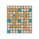 Live, love every day spelled out on a game board. Letter tiles message design. Yellow, pink and blue Stock Image