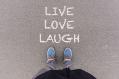 Live, Love, Laugh text on asphalt ground, feet and shoes on floo Royalty Free Stock Image