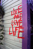 Live and Love Life (Nimbin Graffiti). Some important words painted on the side of a store in Nimbin, Australia stock images