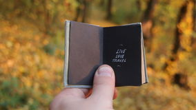 Live love travel, tour packages idea. Hand holding a book with text live love travel stock video