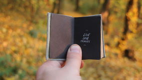 Live love travel, vacation packages idea. Hand holding a book with text stock video