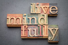 Live mindfully in wood type. Live mindfully - word abstract in letterpress wood type against gray slate stone Royalty Free Stock Photos