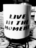 Coffee cup with a meaningful text. Live in the moment royalty free stock images