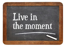 Live in the moment. I- inspirational advice on a vintage slate blackboard stock image