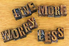 Live more worry less message letterpress. Live more worry less sign message encouragement letterpress block letter words wood background inspirational Stock Image