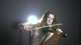 Live music, long-haired female playing on violin at evening event. Fashion musician, long-haired female playing on violin at evening event close-up stock video footage