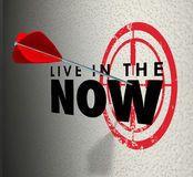 Live in the Now Arrow Hitting Target Aim Enjoy Present Moment. Live in the Now words on a target wall and arrow aiming and hitting the bulls-eye to illustrate Stock Photography