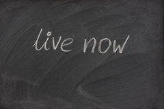 Live now phrase on blackboard Stock Images