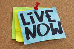 Live now reminder. On blue sticky note posted on cork board Stock Images