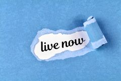 Live now word. The text live nown behind ripped blue paper Royalty Free Stock Photos