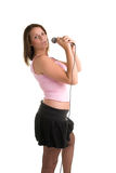 Live Perfomance. Young woman with microphone against white background Stock Photography