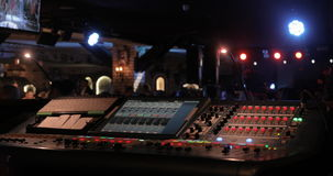 Live performance concert elements, including mixing console, stage lights, and speakers and guitar player.