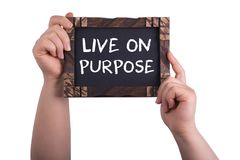 Live on purpose. A woman holding chalkboard with words live on purpose isolated on white background Royalty Free Stock Photography