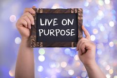 Live on purpose. A woman holding chalkboard with words live on purpose on bokeh light background Royalty Free Stock Photography