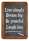 Live simply, dream big, be grateful, laugh lots. Motivational words on a vintage slate blackboard stock photos