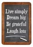 Live simply, dream big, be grateful, laugh lots. Motivational words on a vintage slate blackboard Stock Photos
