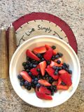 Live Simply mat with white bowl of strawberries and blueberries and candles royalty free stock photography