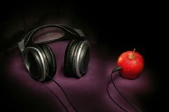 Live sound. Black headphones, red apple, black connector is plugged into the apple dark background music sound combination Stock Photos