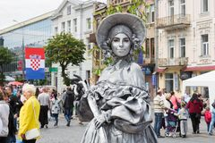 Live statue in a hat on the background of people, buildings and the flag of Croatia at the celebrat stock images