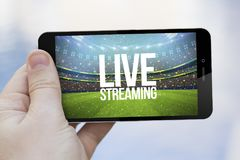 Live streaming cell phone. Live streaming mobile concept: hand holding an live streaming sports event on a 3d generated smartphone. Screen graphics are made up stock photos