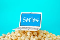 Live streaming series; concepts with text on paper art laptop and.pop corn on pastel color. Background royalty free stock photography