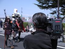Live transmission. Cameraman recording live during a Japanese street festival.  Selective focus on the cameraman Stock Photo