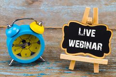 Live webinar - inscription on blackboard with clock on wooden ba. Ckground Royalty Free Stock Photos