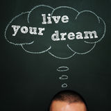 Live your dream. A man over a blackboard with a blank thought bubble drawn in it and the sentence live your dream Royalty Free Stock Photos