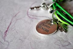 Live your dream. A closeup of a cord bracelet with a charm that says 'Live your dream Royalty Free Stock Photos