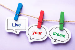 Live your dream. Paper bubbles with clip hanging on the line against purple background royalty free stock image