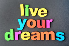Live your dreams on black background. Text Live your dreams on black background stock image