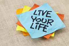 Live your life reminder. Live your life - spiritual reminder - handwriting on a blue sticky note against canvas Royalty Free Stock Photos