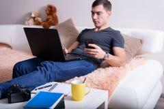 Livefoto des Kerls, der auf der Couch mit einem Laptop und einem Smartphone, nahe bei den Tabellennotizbüchern und einer Kamera s Lizenzfreie Stockbilder