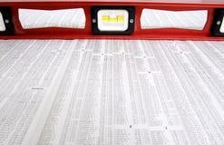 Livella a bolla rossa sulle tavole delle azione del giornale Fotografia Stock