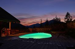 Livello all'aperto ovale della piscina nelle montagne contro il contesto di bei tramonto e montagne di estate E immagini stock libere da diritti