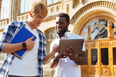 Lively analytical friends discussing their project. I like that. Two active determined intelligent men attending college and fulfilling group assignment while Royalty Free Stock Images