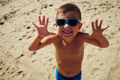 A lively boy in sunglasses smiling at the camera on the beach Royalty Free Stock Photo
