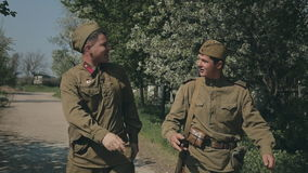 The lively conversation of two young men going to. The war in uniforms with guns stock footage