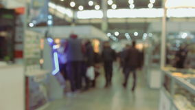 Lively exhibition hall in motion showroom background. The camera passes through the shopping arcade. Trading rows. Background. People go shopping. Lively stock video footage