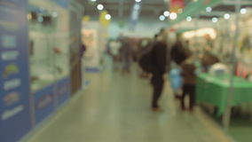 Lively exhibition hall in motion showroom background. The camera passes through the shopping arcade. Trading rows. Background. People go shopping. Lively stock video