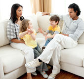 Lively family having fun in the living room. Sitting on sofa Royalty Free Stock Images